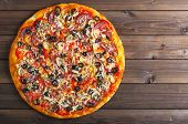 picture of hot fresh pizza  - freshly baked hot pizza on a wooden table - JPG