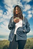 stock photo of hoodie  - Portrait of beautiful young woman with blue hoodie and sportswear holding her smartphone over a cloudy blue sky background - JPG