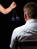 stock photo of pendulum clock  - Woman hypnotizes man with a swinging watch during hypnotic treatment - JPG