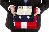 picture of american money  - Businessman holding american flag with stack of money on top - JPG