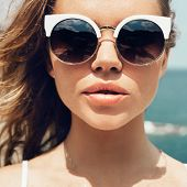 pic of sunbather  - Closeup fashion summer portrait of pretty young sensual woman in sunglasses posing on the beach on vacation