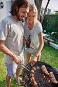 picture of tong  - Women helping boyfriend husband at outdoor garden barbecue with tongs and beer - JPG