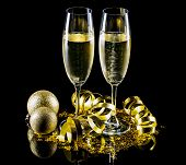 picture of flute  - Champagne flutes with golden Christmas decoration isolated on a black background - JPG