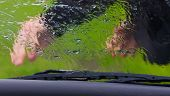 stock photo of wiper  - the man in the rain repairs a window wiper by car - JPG