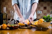 image of sangria  - Man cuts fresh grapefruits for making sangria for home party - JPG