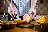 stock photo of sangria  - Man cuts fresh grapefruits for making sangria for home party - JPG