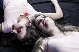 foto of bruises  - Two young beaten women with cuts and bruises lie down on the floor on black background - JPG
