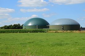 picture of biogas  - biogas plant for renewable energy on a green meadow against the blue sky with clouds - JPG
