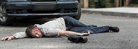stock photo of street-walker  - Dead young man is lying on street - JPG