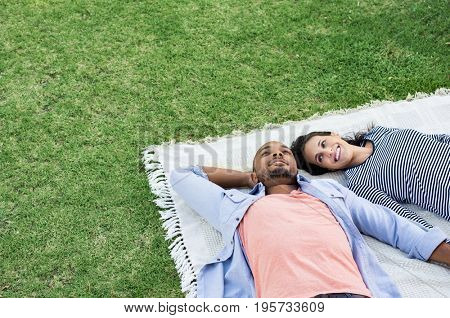 poster of Young multiethnic couple lying on blanket on grass. Latin woman with her african boyfriend relaxing