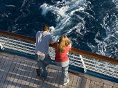stock photo of cruise ship  - Young honeymoon couple on the stern of a cruise ship - JPG