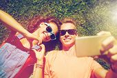 love and people concept - happy teenage couple in sunglasses lying on grass and taking selfie on sma poster
