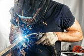 Man Weld  A Metal  With A  Welding Machine poster
