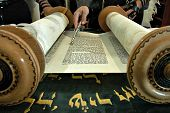 stock photo of torah  - Torah reading in a synagogue with a hand holding a silver pointer - JPG