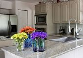 image of flower vase  - modern grey kitchen with vases of flowers on countertop  - JPG