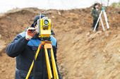 stock photo of theodolite  - Surveyor worker make data collection with total station theodolite at construction site - JPG