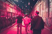 People Walking On Street At Night In Nightlife Area - Blurred poster