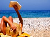 stock photo of pretty girl  - Pretty girl reading novel at beautiful beach - JPG