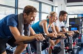 Group of smiling friends at gym exercising on stationary bike. Happy cheerful athletes training on e poster