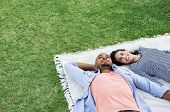 Young multiethnic couple lying on blanket on grass. Latin woman with her african boyfriend relaxing  poster