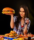 Woman eating hamburger. Student consume fast food. Girl bite of very big burger. Girl trying to eat  poster