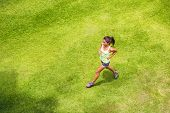 Active sport woman runner running on grass outdoor training for marathon. Asian chinese sporty girl  poster