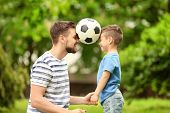 Dad and son with soccer ball in green park poster