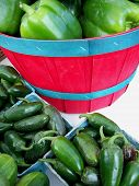 stock photo of gleaning  - Variety of fresh green peppers on display at the weekly market - JPG