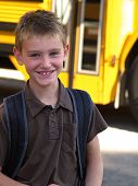 picture of school child  - a smiling school boy with a yellow school bus in the background - JPG