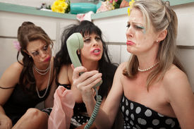 stock photo of pep talk  - Pouting woman on phone with friends in kitchen - JPG