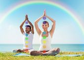 mindfulness, spirituality and outdoor yoga - couple meditating in lotus pose with seven chakra symbo poster