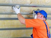 pic of attic  - Construction worker thermally insulating house attic with mineral wool - JPG