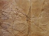 stock photo of babylonia  - Ancient Assyrian wall carvings of men on a Royal lion hunt