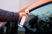 Man After Washing Uses Anti-rain Spray For Car Glass Windows. Male Hand And Car Body Close Up. Orang poster
