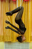 Sporty girl posing with aerial hoop. Woman in black clothes doing entertainment exercise with aerial poster