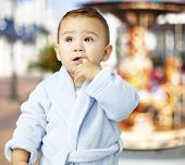 image of housecoat  - portrait of an adorable infant with his finger in his mouth wearing a bathrobe - JPG