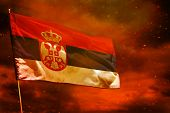 Fluttering Serbia Flag On Crimson Red Sky With Smoke Pillars Background. Serbia Problems Concept. poster
