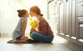 Happy Mothers Day! Child Daughter   Gives Mother A Bouquet Of Flowers To Narcissus And Gift. poster
