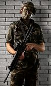 portrait of a young soldier with jungle camouflage holding a rifle against a grunge brick wall