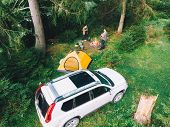 Couple Sitting Near Campfire Drinking Tea. Yellow Tent And White Suv Car. Active Leisure Time poster