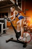 Athletic Young Woman Exercise On Cardio Machine Or Bycicle In The Gym. poster