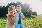 Mother And Little Son Blowing Soap Bubbles Outdoor poster
