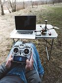 Fpv Drone Pilot. A Man Sits In A Chair With A Remote From The Fpv Drone In Front Of A Laptop And Con poster