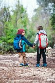 Two Boys With Backpacks Are Walking Along A Forest Path. Children Walk In The Park. Friends Travel T poster