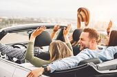 Group Of Friends Having Fun In Convertible Car During Road Trip At Sunset - Young Travel People Driv poster