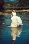 Pretty Bride Pretty Woman In Long Elegant White Lace Wedding Dress Stands In Lake Water Sunny Day Ou poster