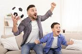 Emotional Father And Son Soccer Fans Cheering With Football Ball, Watching Sport On Tv At Home poster