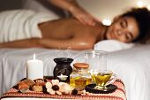 African Woman Enjoying Aromatherapy Massage In Luxury Spa With Candles On Foreground poster