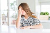 Beautiful young girl kid wearing stripes t-shirt tired rubbing nose and eyes feeling fatigue and hea poster