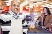 picture of cashiers  - Portrait of a grocery store cashier standing at checkout counter with customers in the background - JPG
